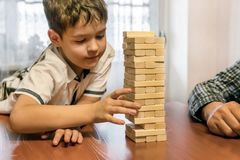 Father and focused son playing jenga game at home royalty free stock images