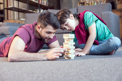 Father and focused son playing jenga game at home. Smiling father and focused son playing jenga game at home Stock Images