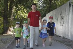 Father walks on the street with his childs on father`s day. Father and four of his children are walking along the street. happy family on father`s day royalty free stock image