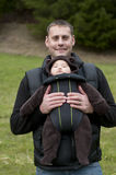 Father with Front Baby Carrier. Father with a front baby carrier, holding his newborn son in a cute little pouch in front of his chest Royalty Free Stock Photography