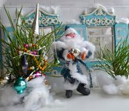 Father Frost is decorating the New Year tree. Cute Santa Claus in blue costume is decorating the New Year tree Royalty Free Stock Photo