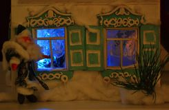 Santa and shining windows. Father Frost is looking in the new year night windows Stock Photos