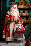 Father Frost and Snow Maiden standing with gifts Royalty Free Stock Photo