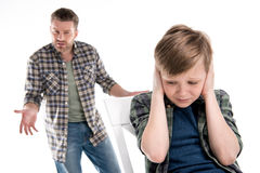 Father gesturing and quarreling with scared little boy closing ears Stock Images