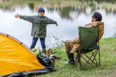 Father and son in camping at lake. Father and gesturing son at tent in camping at lake Stock Photos