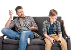Father gesturing and talking to little son sitting on sofa and using smartphone. Family problems concept stock images