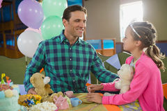 Father and girl interacting while playing toy kitchen set Royalty Free Stock Photo