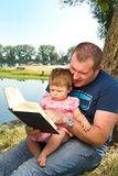 Father and girl reading book Stock Image