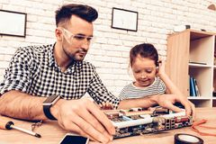 Father and Girl Repair Device on Table at Home stock images