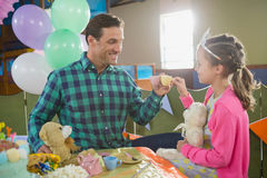 Father and girl toasting their tea cups while playing with toy kitchen set Royalty Free Stock Photo