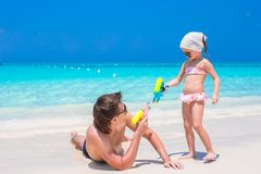 Father and girl at tropical beach having fun. Happy father and his adorable daughter at tropical beach having fun Stock Photo