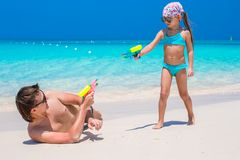 Father and girl at tropical beach having fun. Happy father and his adorable daughter at tropical beach having fun Royalty Free Stock Images
