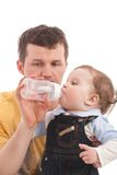 Father give drink her son by feeding bottle Royalty Free Stock Images