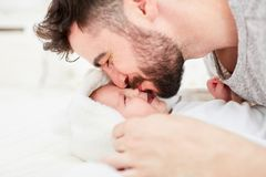 Father gives baby a kiss on the forehead. Happy father gives a kiss to his newborn baby on the forehead Stock Photo