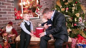 Father gives a Christmas gift sons, Children watching gifts from parents good father spends Christmas Eve with the stock video