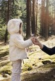 Father gives a flower crocus to his little girl. Father and daughter on a mountain walk, pine forest with wildflowers Royalty Free Stock Photography