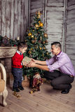 Father gives a gift to his son under the Christmas tree stock images