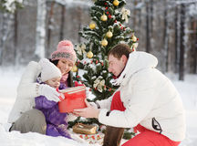 Father gives his daughter a gift for Christmas in winter forest Royalty Free Stock Photo