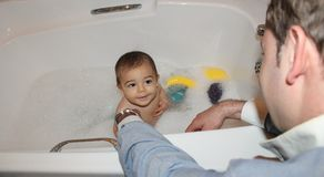 Baby boy taking a bath with foam with help of his daddy royalty free stock photos