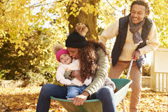 Father Gives Mother And Daughter Ride In Wheelbarrow Stock Images