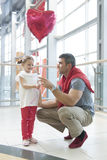Father gives young daughter heart shaped balloon Royalty Free Stock Images