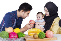Father giving an apple to baby Stock Images