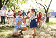 Father giving a cake to a small daughter on a family celebration or a birthday party. Family celebration outside in the backyard. Father giving a cake to a royalty free stock photos