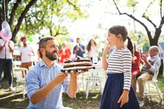 Father giving a cake to a small daughter on a family celebration or a birthday party. royalty free stock images