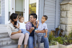 Father Giving Children Candy On Steps Outside Hose royalty free stock image