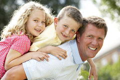 Father giving children piggyback Stock Image