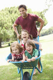 Father Giving Children Ride In Wheelbarrow Royalty Free Stock Photography