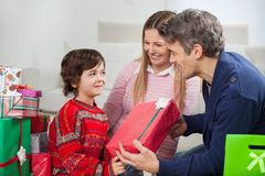 Father Giving Christmas Gift To Son. Happy father giving Christmas gift to son with mother sitting by at home Royalty Free Stock Image