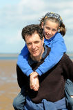 Father giving daughter a piggy back. Portrait of father and daughter at beach royalty free stock photo