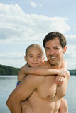 Father giving daughter a piggyback Royalty Free Stock Photography