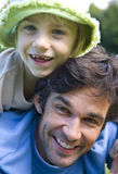Father giving daughter (5-7) piggyback, girl wearing hat, smiling, portrait, close-up Royalty Free Stock Image