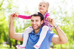 Father Giving Daughter Piggyback Ride. Father and Daughter playing outdoors Royalty Free Stock Image