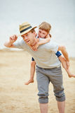 Father giving daughter piggyback ride in summer Stock Photo