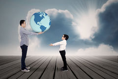 A Father giving the earth to his son. Young father passing the earth to his son royalty free stock image