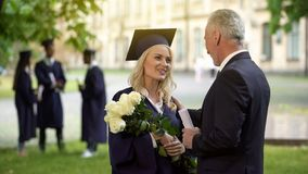 Father giving flowers to his graduate daughter, congratulations, paternal pride. Stock photo stock photography