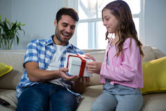 Father giving gift to daughter in the living room Royalty Free Stock Photos