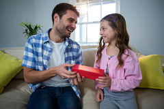 Father giving gift to daughter in the living room Royalty Free Stock Images