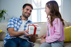 Father giving gift to daughter in the living room Stock Photos