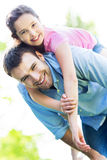 Father giving his daughter a piggyback Stock Image