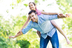 Father giving his daughter a piggyback Stock Photo