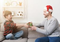 Father giving his son a christmas present at home. Father in santa hat giving his son a christmas present at home in the living room royalty free stock photo