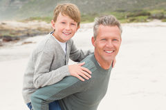 Father giving his son a piggy back Royalty Free Stock Images
