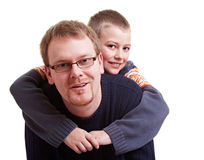 Father giving his son a piggyback. Father giving his happy son a piggyback ride Royalty Free Stock Images