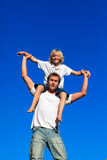 Father giving his son a piggyback ride. Against the blue sky Stock Photography