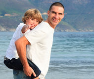 Father giving his son piggyback ride on the beach. Smiling Royalty Free Stock Photography