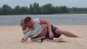 Father giving his son piggyback ride at the beach stock footage
